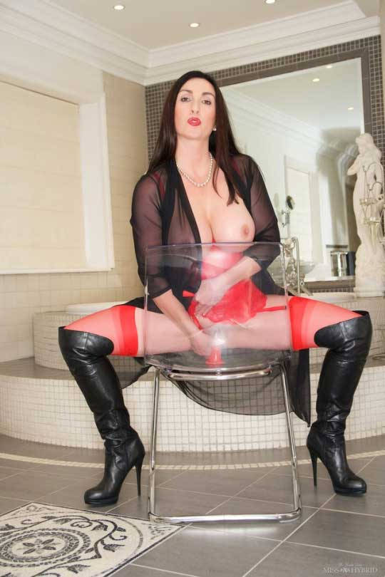 Mistress Miss Hybrid in leather thigh boots sitting astride clear perspex chair.