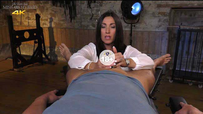 Miss Hybrid plays with her victims caged cock in the dungeon.