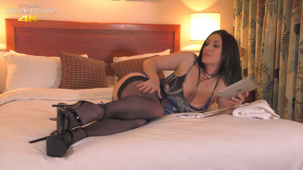 Miss Hybrid glass toy, sexy stockings and high heels films herself on the bad.