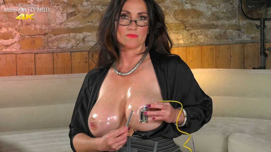 Miss Hybrid oily tits and stiletto heels removes her leather gloves to tighten her HD nipple clamps.