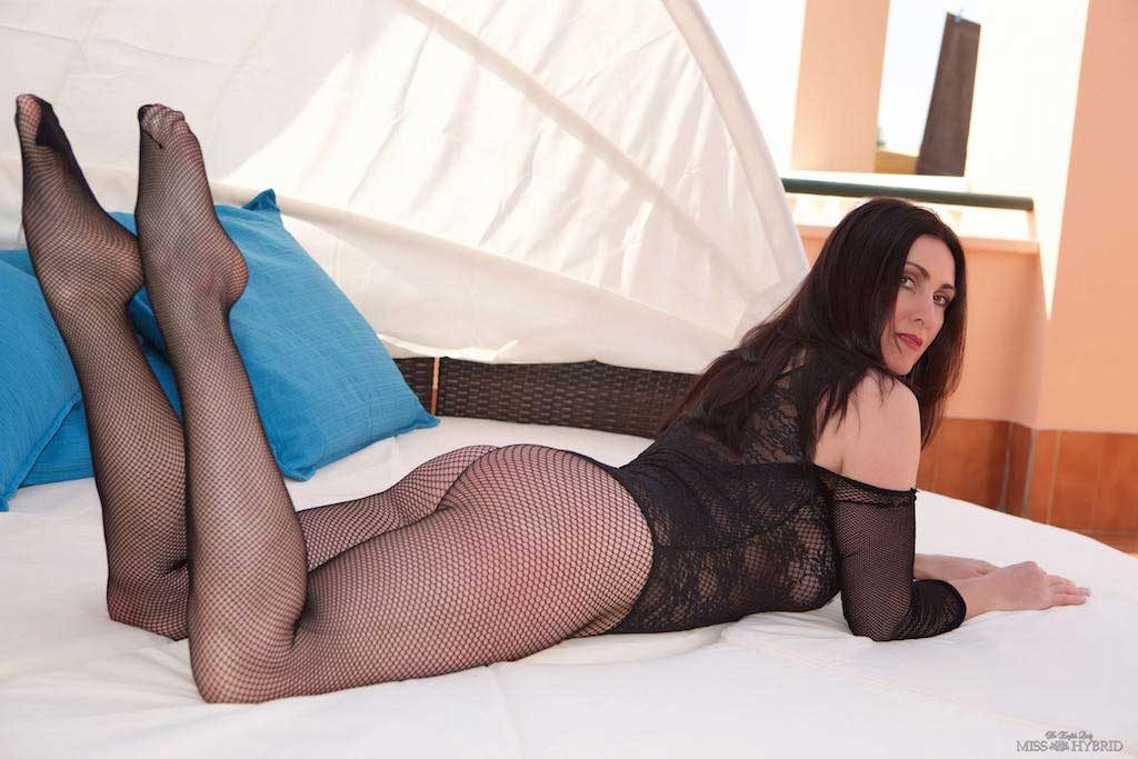 Miss Hybrid fishnets body stocking and huge tits on the patio.